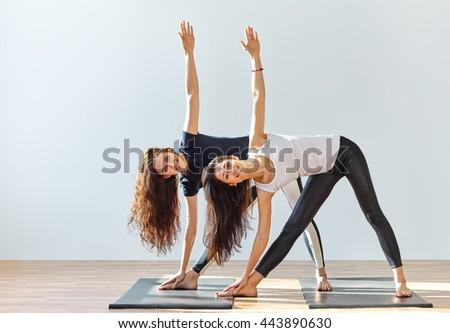 Two young women doing yoga asana extended triangle pose. Trikonasana - stock photo