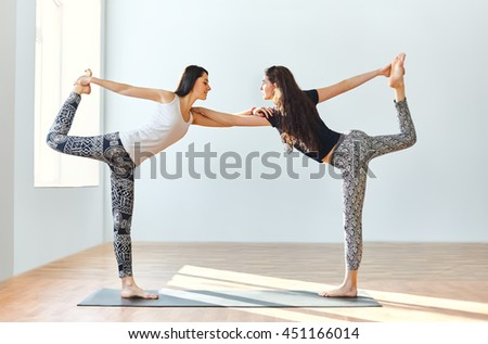 Two young women doing yoga asana lord of the dance pose. Natarajasana  - stock photo