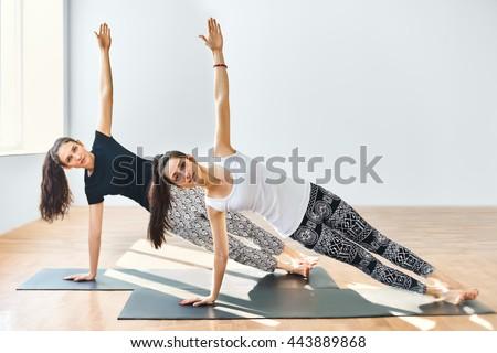 Two young women doing yoga asana side plank. Vasisthasana - stock photo
