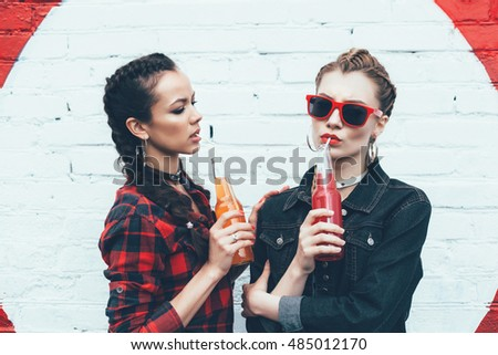Two young women drinking colorful cocktails from bottles in the street. Fashionable style, hairstyle with braids. Outdoors lifestyle toned portrait
