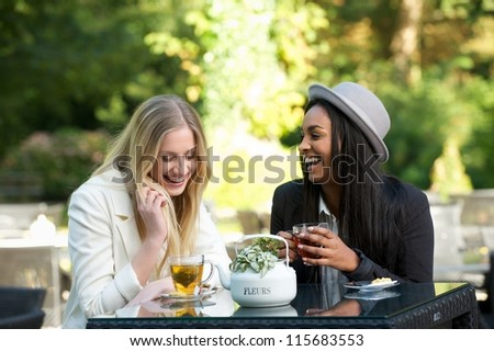 Two young women drinking tea and gossiping