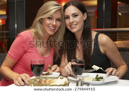 Two Young Women Enjoying Meal In Restaurant - stock photo