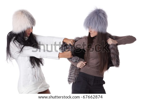 Two young women fighting for magnificent fur's coat on a white background. Sale. - stock photo