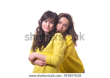 two young women friends in yellow sweater with cups in their hands talking and laughing isolated on white background.
