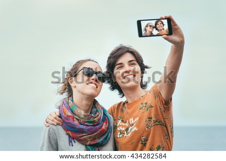 Two young women friends taking a selfie by the sea on summer. Cheerful firiends enjoying sunny day by the sea. - stock photo