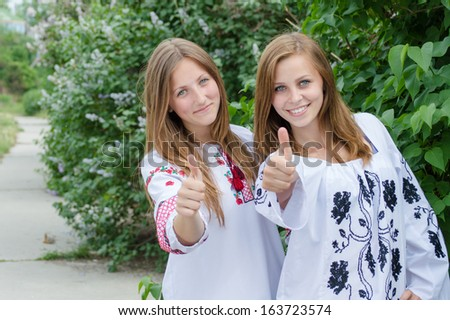 Two young women girl friends giving thumbs up happy smiling & looking at camera on summer outdoors background - stock photo