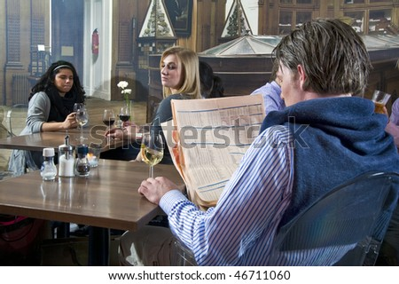 Two young women glancing at a neighboring man in a restaurant - stock photo
