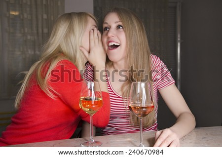 Two young women gossiping, while drinking. Telling a secret - stock photo
