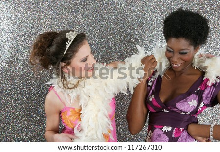 Two young women having a party and being playful against a silver glitter background. - stock photo