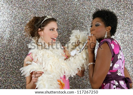 Two young women having a party and blowing whistles against a silver glitter background, - stock photo