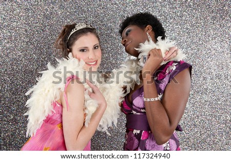 Two young women having a party and dancing against a silver glitter background. - stock photo