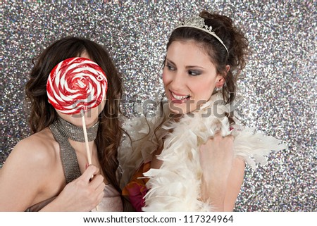 Two young women having a party dressing up and using a large candy to hide the face of one.