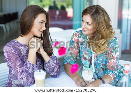 Two young women having coffee break - stock photo
