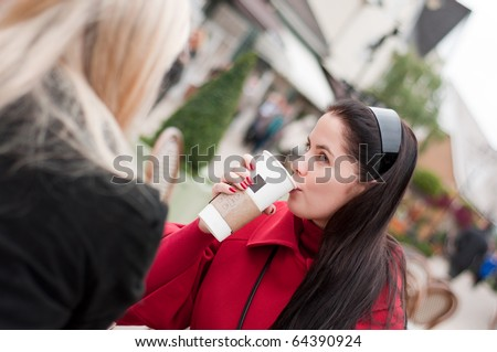 Two young women having coffee break together after shopping