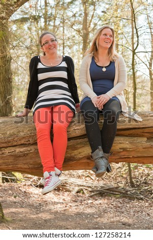 Two young women having fun in forest.