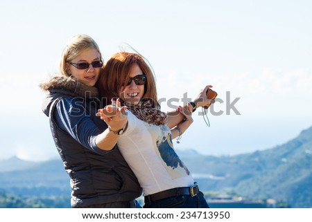 Two young women having fun outdoors - stock photo