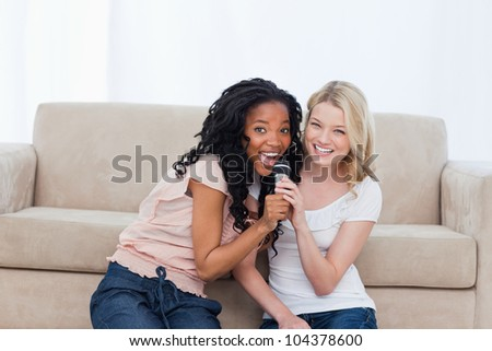 Two young women holding a microphone are sitting on the floor - stock photo