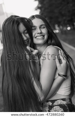 Two young women hugging and smiling with closed eyes outdoors. Black and white