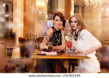 two young women in a bar talking about a secret - stock photo