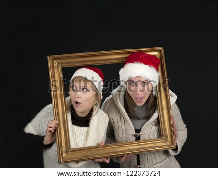 two young women in a frame, on black background - stock photo