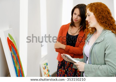 two young women in a gallery and contemplating abstract artwork