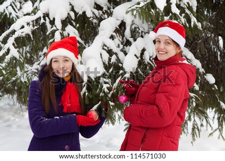 Two  young women  in  christmas hats decorates  spruce outdoors - stock photo