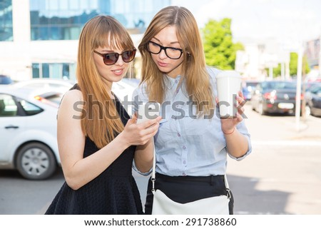 Two young women in glasses looking at mobile phone together while standing outdoors. Two beautiful women sending messages with mobile phone. Urban women are discussing the news and read in smart phone - stock photo