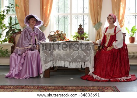 Two young women in historical clothes poses indoor - stock photo