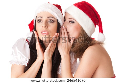 Two young women in Santa costume on a white background. Female secrets. - stock photo