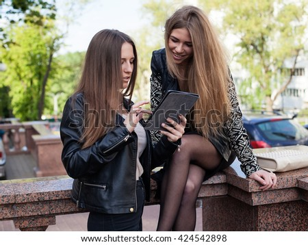 Two young women in the city are looking at the   the screen  of a tablet and smiling - stock photo