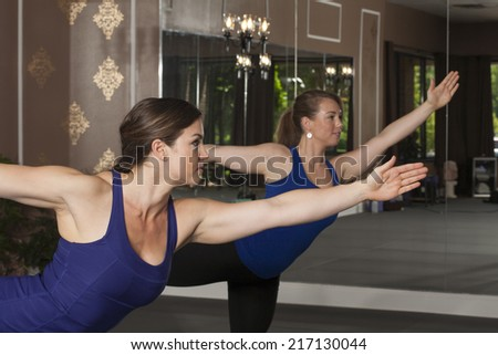 Two Young Women in Yoga Pose - stock photo