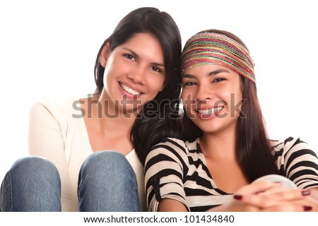 Two young women looking at the camera smiling, white background - stock photo