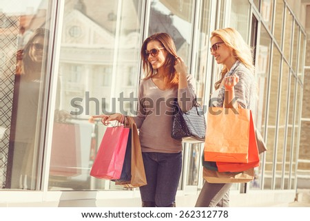 Two young women looking in showcase - stock photo