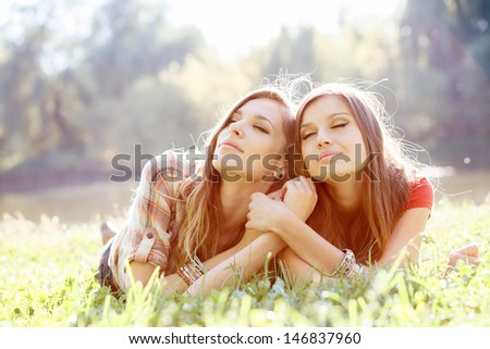 two young women lying down on grass with eyes closed resting - stock photo