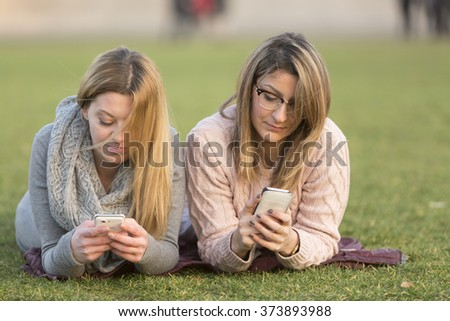 Two young women lying down on their stomach typing on a cell phone - stock photo