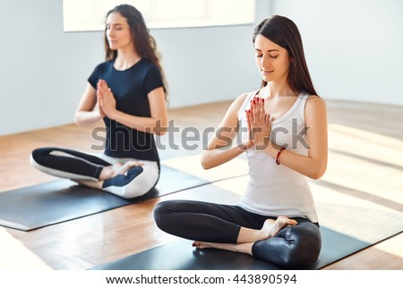 Two young women meditating in lotus pose with hands in namaste. Yoga - stock photo
