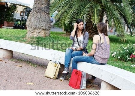 Two Young Women on a Bench at Park , Italy - stock photo