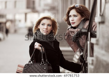 Two young women on a city street - stock photo