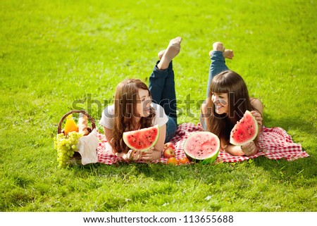 Two young women on a picnic with watermelon - stock photo