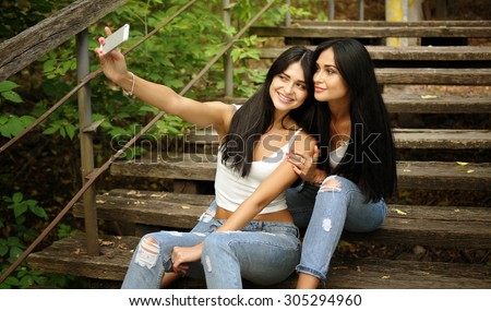 Two young women on the wooden stairs making selfie with mobile phone - stock photo