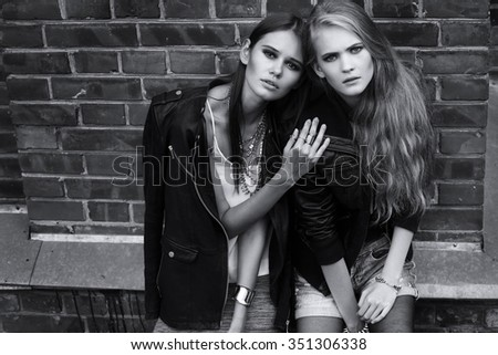 Two young women posing outdoor. Street fashion. Black and white image.