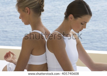 Two young women practicing yoga - stock photo
