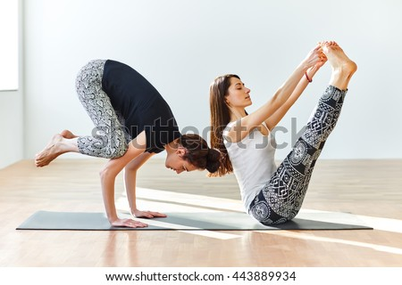 Two young women practicing yoga poses and asanas. Partner yoga - stock photo
