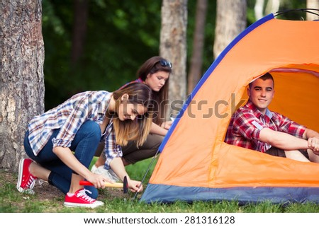 Two young women putting up a tent with a smiling young man sitting in it - stock photo