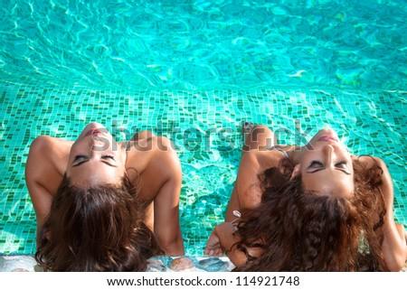 two young women relax and take sunbath in swimmingpool - stock photo