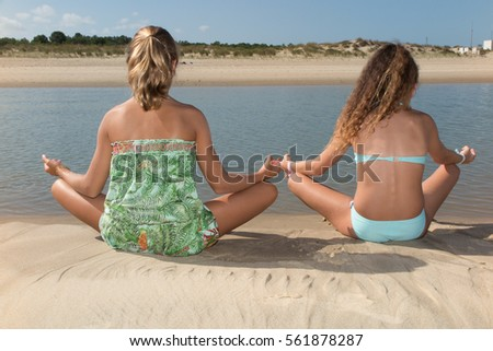 Two young women relax in front of the sea in yoga posture
