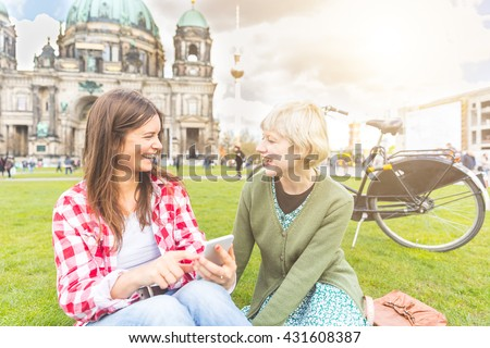 Two young women relaxing in Berlin with the Cathedral and Fernsehturm tv tower on background. They have a smart phone and they are looking each other smiling. Friendship and lifestyle concepts.