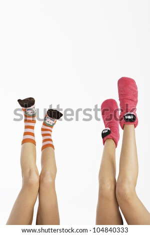 Two young women's legs up in the air wearing funny socks.