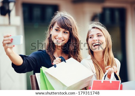 "Two young women shopping at the mall taking a ""selfie"" or self portrait with their cell phone - stock photo"
