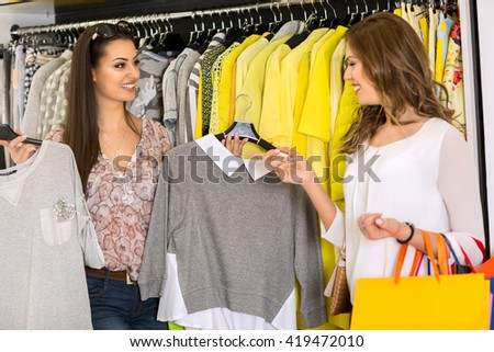Two Young Women Shopping in a Store choosing clothes